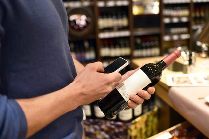 Botella de vino con tag NFC y usuario escaneando